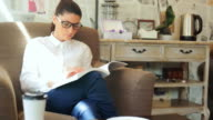 Pretty young woman reading a book in a teahouse. video