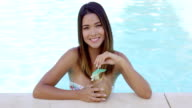 Pretty young woman relaxing in a resort pool video