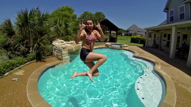 Pretty young woman smiles and jumps into backyard swimming pool video
