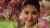 Pretty young woman smiling, shot through flowers video