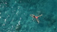AERIAL: Pretty young woman swimming in amazing ocean and watching surroundings video