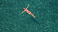 AERIAL: Pretty young woman swimming starfish float in crystal clear ocean lagoon video