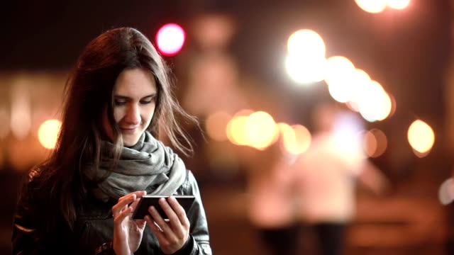 Pretty young woman using her smartphone at night. Lady in the street in cold weather. Modern technology video