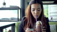 Pretty young woman using smart phone in restaurant video