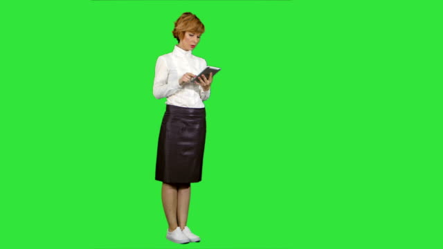 Pretty young woman using tablet on a Green Screen, Chroma Key video
