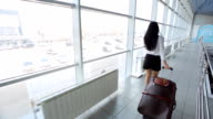 Pretty young woman walks through airport with luggage video