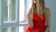 Pretty young woman with wreath of red flowers on her head sitting on windowsill, smiling, cam moves upward, slow motion video