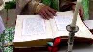 priest reading Bible video