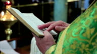 Priest reading the Bible in church. priest shatters the scriptures holy bible video