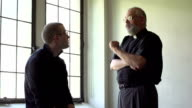 Priest talking with parishioner in a church video