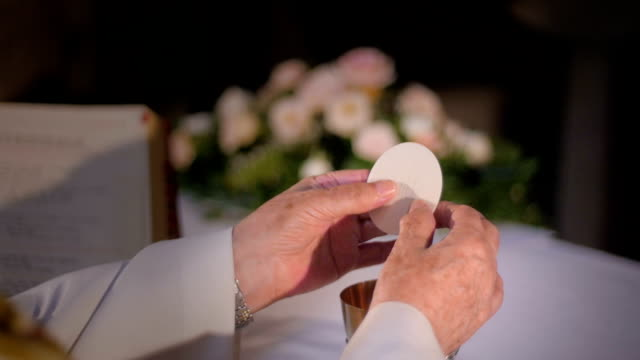 Priest's hands breaking the wafer video