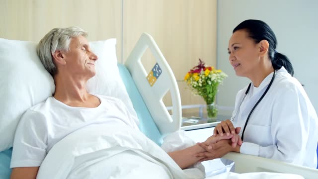 Prifessional positive femle doctros sitting near hospital bed video