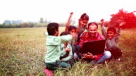 Primary School Students with Teacher sitting in the field holding laptop video