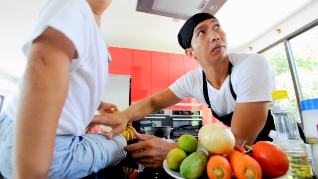 Private Thai chef cooking, his little son in chef's hat nearby sitting on the table in a modern style home kitchen video