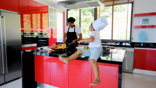 Private Thai chef cooking, his little son in chef's hat nearby sitting on the table in a modern style home kitchen. Kid is eating, dad making food video