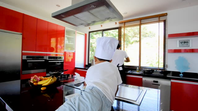 Private Thai chef cooking, his little son in chef's hat nearby sitting on the table in a modern style home kitchen. Rear view. Faces hidden video