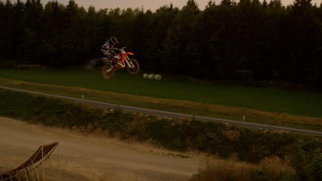AERIAL SLOW MOTION: Pro motocross biker riding and jumping no hander superman video
