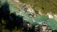 AERIAL: Pro paddlers in red, orange and blue kayak paddling on whitewater river video