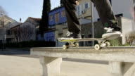 CLOSE UP: Pro skateboarder performing 50-50 grind trick sliding on a bench video