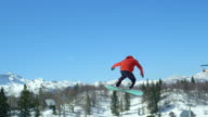 SLOW MOTION CLOSEUP: Pro snowboarder jumping big air kicker in sunny winter on a snowy mountain video