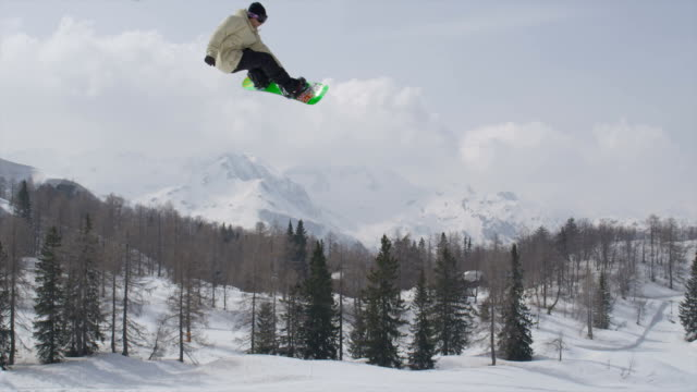 AERIAL SLOW MOTION: Pro snowboarder jumping big air kicker video