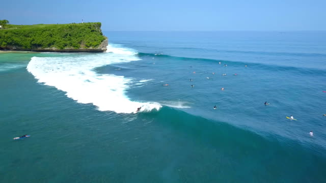 AERIAL: Pro surfer riding huge foamy wave in beautiful sea in crowded sunny Bali video