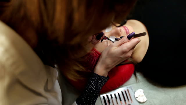 Procedure of eyelashes extension in salon.Close-up video