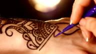 Process of applying mehndi on hand close up, back light, black video