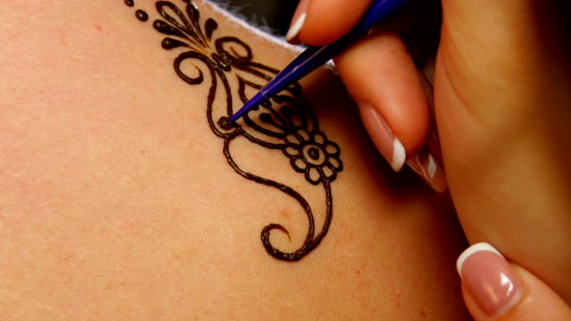 Process of decorating woman`s back with henna tattoo, mehendi, on black video