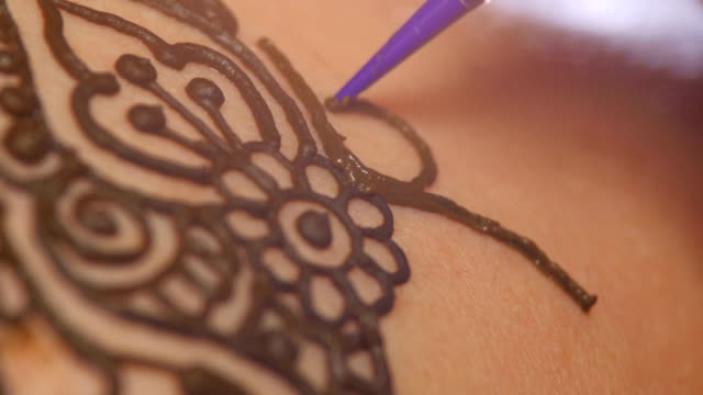 Process of decorating woman`s back with henna tattoo, mehendi, on black, dynamic change of focus video