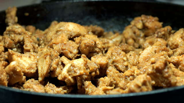 Process of frying chopped chicken pieces. Close-up video