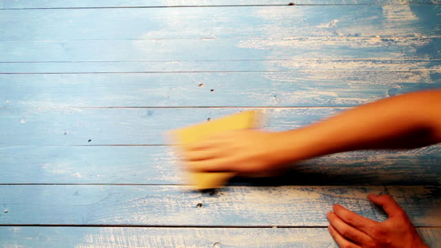 A process of polishing a wooden board with sandpaper in order to make it look older video