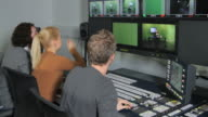 Producers working in television studio control room video