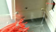 Production of cables and harnesses. Red cables fall to the floor of the installation video