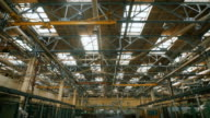 Production premise with a high ceiling and a large number of industrial equipment throughout the territory. Many metal structures, ventilation pipes used in building construction. Big light windows in the roof are used for lighting in the daytime video