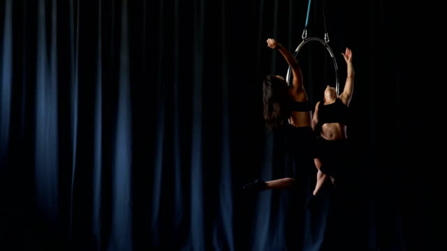 Professional acrobats performs a gymnastic trick on the aerial hoop video