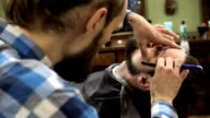 Professional barber shave client's beard with straight razor. very concentrated. FullHD video