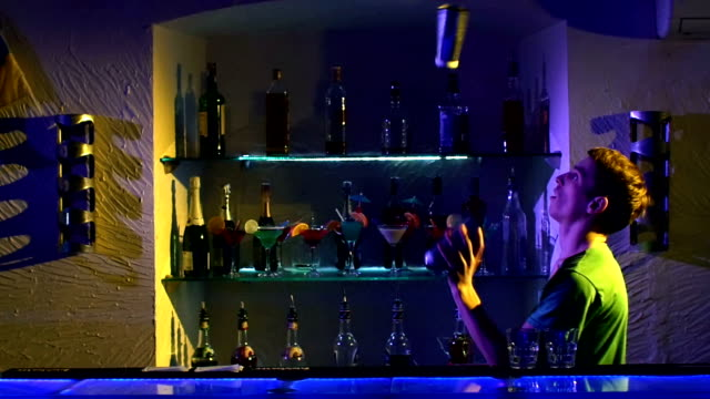 Professional bartender making cool, amazing tricks three shakers, juggling standing behind the bar, catching, throwing up, slow motion video