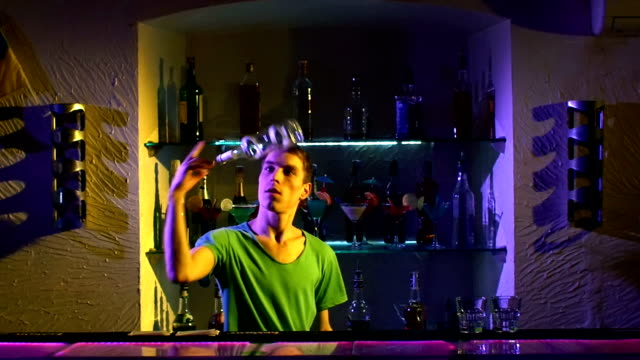 Professional bartender making cool tricks with two glasses, shaker and bottle standing behind the bar, catching on elbow, throwing up, slow motion video