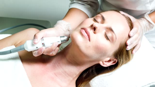 Professional beautician massaging female face by device video