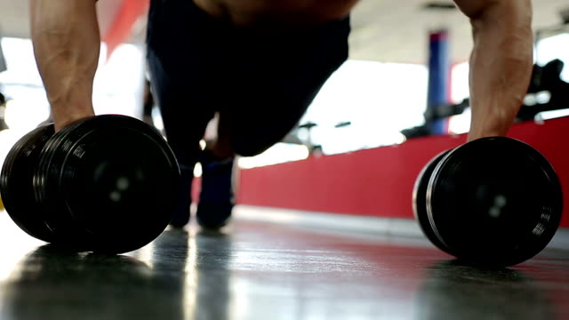 Professional bodybuilder doing dumbbell push-ups, training hard during workout video