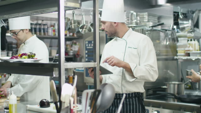 Professional chef in a commercial kitchen in a restaurant or hotel is using a tablet computer. video