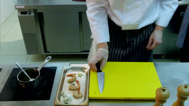 Professional chef's hands putting chopped mushrooms together with shrimps and stirring sauce video
