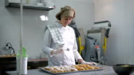 Professional confectionery sprinkled with powdered sugar freshly baked eclair in the kitchen at the bakery. Equipment for the preparation of sweets on the background video