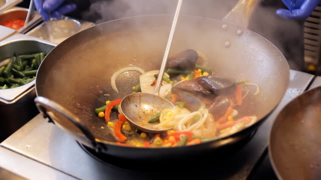 Professional cook is frying mussels and shrimps with vegetables at the street food festival. Roasted prawns and mollusk close up. Cooking process of sea food. Traditional asian food video