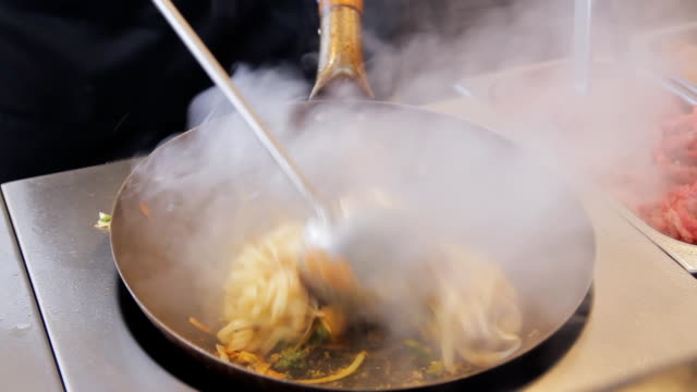 Professional cook is frying noodles with vegetables and meat at the street food festival. Stir fry with beef and vegetables close up. Process of cooking. Traditional asian food video