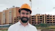 Professional engineer, constructor at work in construction site, looking at camera. Portrait video