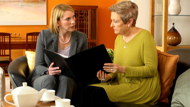 Professional Explains Documents to Senior Woman video