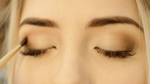 Professional Eye makeup artist applying eyeshadow powder. Beautiful woman face. Perfect makeup. Beauty fashion. Eyelashes. Close up video