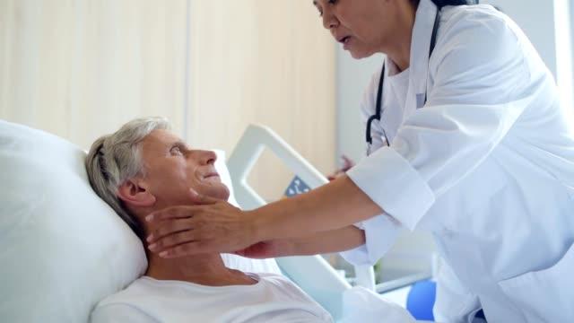 Professional female doctor examing a senior sick man video